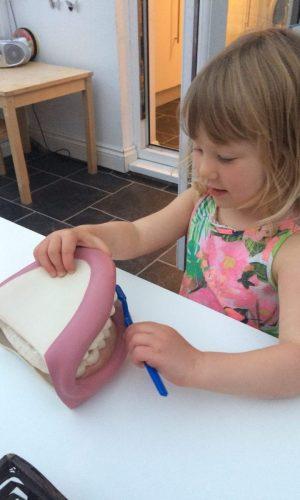 Thoroughly enjoying brushing the Montessori teeth